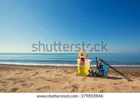 Young hiker woman on the sandy beach to the sea to enjoy the scenery. Traveling to the active vacation.