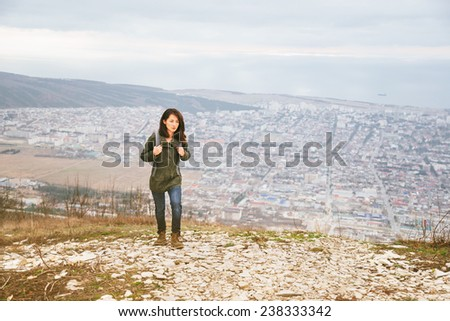 Young hiker woman with backpack walking in highlands over the city. Hiking and recreation theme - stock photo