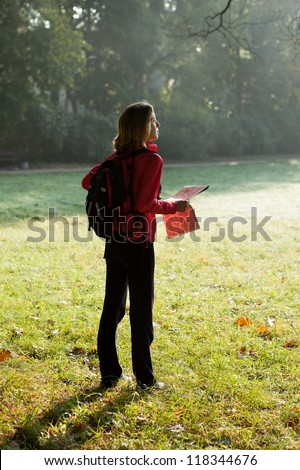 Young hiker woman with map in hands in the morning sun rays among the green nature - stock photo