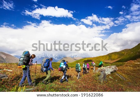 Young hikers trekking in Svaneti, Georgia. Shkhara mountain in the background. Amazingly beautiful WORLD. Fantastic sky background with blue clouds. - stock photo