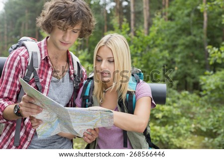 Young hiking couple reading map together in forest - stock photo