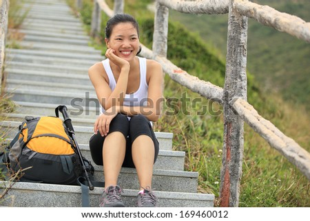 young hiking woman sit on mountain rock have a rest