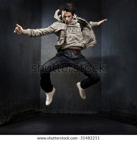 Young hip-hop dancer over a grunge wall - stock photo