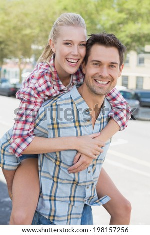 Young hip man giving his blonde girlfriend a piggy back on a sunny day in the city - stock photo