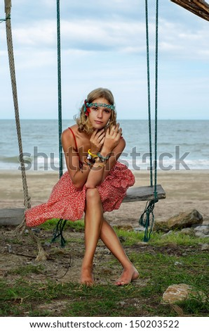 Young hippie on a swing - stock photo