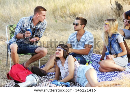 Young hippie people relaxing in the forest outdoors