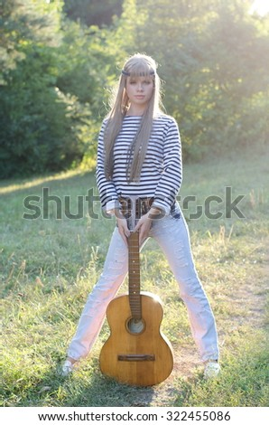 Young hippie-style girl with a guitar on a meadow of green grass. Warm summer evening.   - stock photo