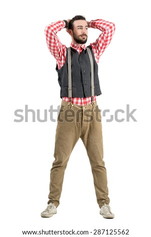 Young hipster adjusting hair with hands looking at distance. Full body length portrait isolated over white studio background.  - stock photo