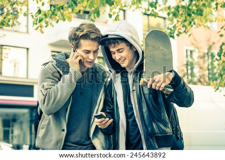 Young hipster brothers having fun with smartphone - Best friends sharing free time with new trends technology - Guys enjoying everyday life moments texting connected with modern smart phone device - stock photo