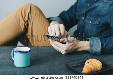 young hipster checking his mobile phone while having a breakfast - stock photo