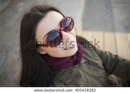Young hipster chick in grey parka coat, sunglasses and marsala scarf posing outdoors at day. Cute young model and trendy youth fashion clothes.  - stock photo