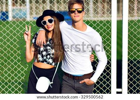 Young hipster couple having fun at summer time, hugs, emotions, wearing stylish black and white clothes and sunglasses, students party, joy, romantic. - stock photo