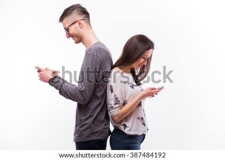 Young hipster couple  in love ignoring each other with phones. Caucasian couple against white background. - stock photo