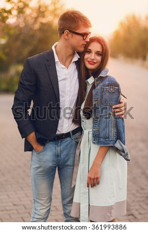 Young hipster  couple in love outdoor.Stunning sensual outdoor portrait of young stylish  couple posing in summer. Pretty young girl in jeans  jacket  and her handsome boyfriend hugging. Sunset. - stock photo