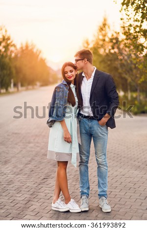 Young hipster  couple in love outdoor. Stunning sensual  portrait of young stylish fashion couple posing in summer sunset  . Pretty young girl in jeans  jacket  and her handsome boyfriend walking . - stock photo