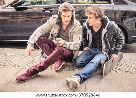 Young hipster fashion brothers having fun using smartphone - Best friends sharing time with smart phone - Everyday life moment with modern device - Light vintage filtered look with soft focus on faces - stock photo