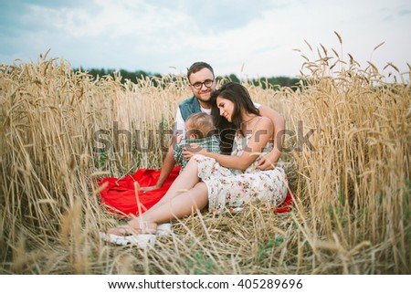 Young hipster father, mother cute baby son on picnic with wigwam on hay field - stock photo