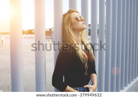 Young hipster girl dressed in cool clothes enjoying beautiful warm spring day and rest after walking outdoors, attractive woman in fashionable sunglasses relaxing in the fresh air during free time - stock photo