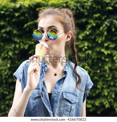 Young hipster girl eating ice cream in summer hot weather in round mirror sunglasses have fun and good mood. Toned style instagram filters - stock photo
