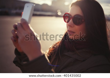 Young hipster girl in grey parka coat and sunglasses taking photo with her trendy smart phone outdoors at bright spring day. Warm film color tones. - stock photo