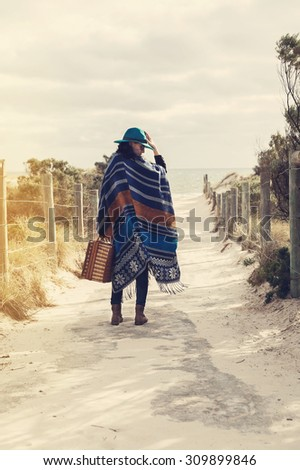 Young hipster girl in poncho with vintage suitcase at the beach. Instagram looking effect, filters, color toning, selective focus - stock photo