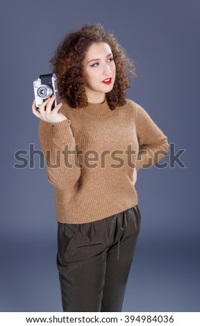 Young hipster girl in sweater with retro photo camera on grey background
