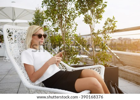 Young hipster girl is chatting on smart phone, while relaxing in bar in the fresh air during her weekend abroad. Blonde female with fashionable look is resting in cafe terrace and using cell telephone - stock photo
