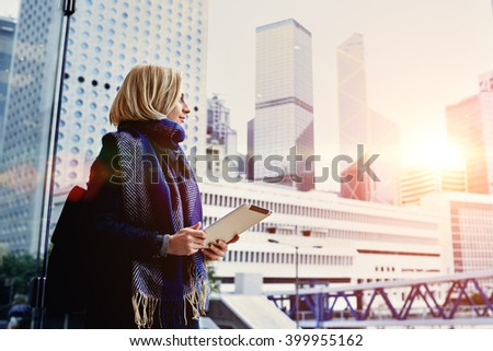 Young hipster girl is holding digital tablet and looking in window at active life of big metropolitan city with tall skyscrapers,background with copy space for your advertising text message or content - stock photo