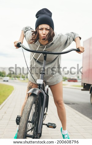 Young hipster girl on black bike making a face at camera. Outdoor lifestyle portrait