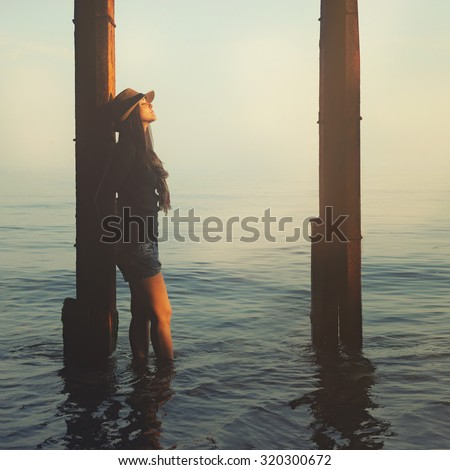 Young hipster girl relaxing under the pier in a sea water.