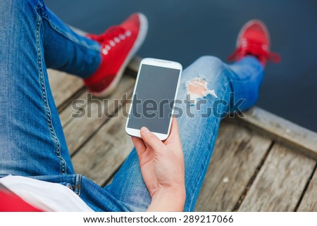 Young hipster girl sitting on a pier and using smart phone - stock photo
