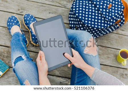young hipster girl using tablet on a wooden floor. Working place outdoor