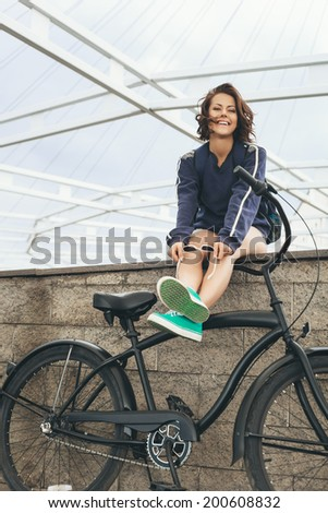 Young hipster girl with black bike looking at camera. Outdoor lifestyle portrait