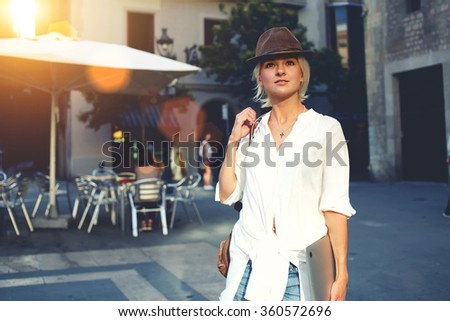 Young hipster girl with closed laptop computer in hands admires something while standing in urban scene in sunny day, thoughtful woman dressed in trendy clothes posing outdoors during recreation time - stock photo