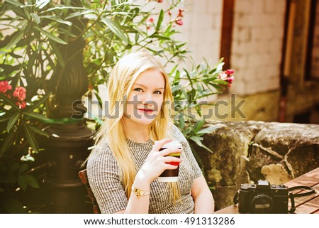 Young hipster girl with cup of coffee sitting at the cafe with vintage camera. Female traveler, travel blogger concept