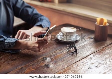 Young hipster guy texting with his mobile phone at the bar and having a cappuccino - stock photo