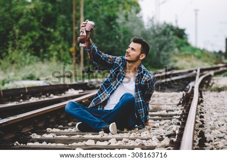 Young hipster guy tourist with camera and bag taking a selfie on the railroad. Vintage Instagram style effect, soft and selective focus, grain texture visible on maximum size - stock photo