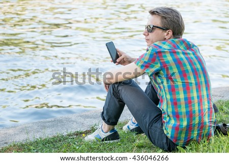 Young hipster in colorful shirt using his smartphone sitting near water in park