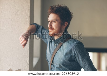 Young hipster looking away and leaning on a wall - stock photo