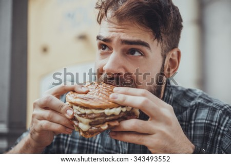 Young Hipster Male In Pub Eating Delicious Burger - stock photo