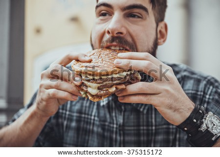 Young Hipster Male In Pub Eating Delicious Burger