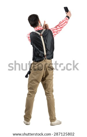 Young hipster male taking selfie with thumbs up rear view. Full body length portrait isolated over white studio background.