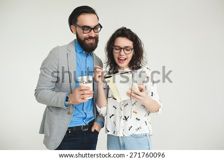 Young hipster man and woman in glasses with smartphone and tablet celebrating success isolated on the blank white background - stock photo