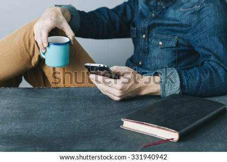 young hipster man having a break with coffee,book and a mobile phone - stock photo