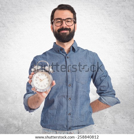 Young hipster man holding a clock - stock photo