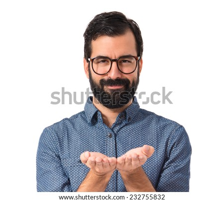Young hipster man holding something over white background   - stock photo