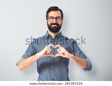 Young hipster man making heart sign - stock photo