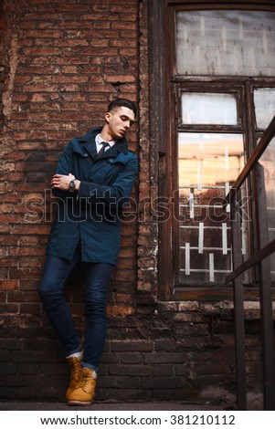 Young hipster man on iron stairs, near old window in sunset. A man wearing in a blue jacket , a white shirt, blue jeans and yellow boots