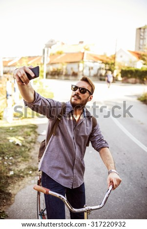 Young hipster man riding vintage bike on city street and taking selfie - stock photo