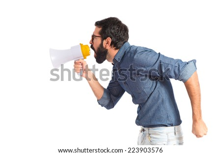 Young hipster man shouting by megaphone - stock photo